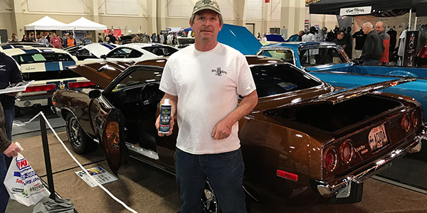 man standing in front of brown car with bottle of Quick Sheen metal polish